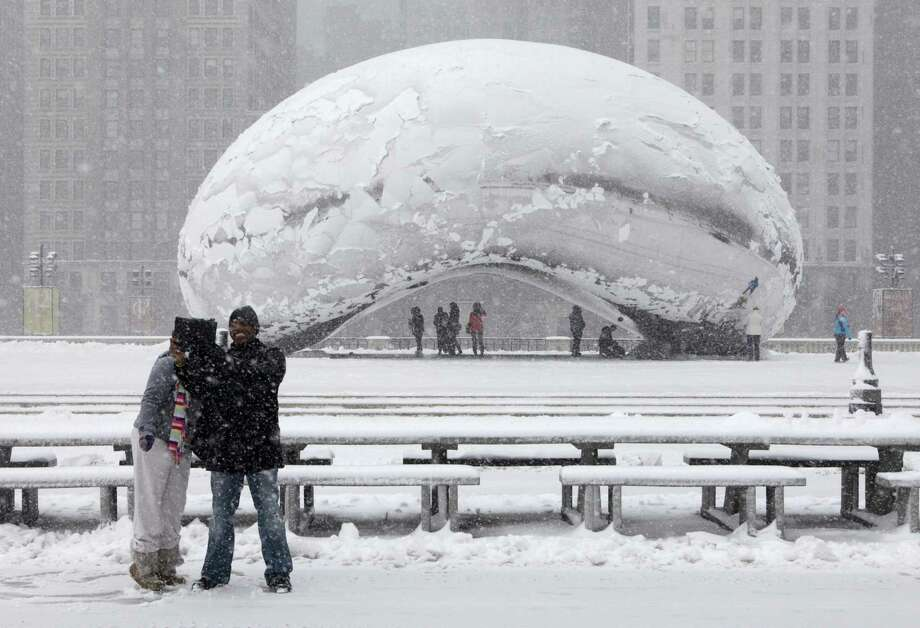 Onlookers take pictures in front of Cloud Gate, a public sculpture by Indian-born British artist Anish Kapoor, as they walk around the Millennium Park as a snow storm passes through the region Tuesday, March 5, 2013, in Chicago. Chicago was hit Tuesday by a storm expected to dump as much as 10 inches of snow in the area before the end of the day — the most since the 2011 blizzard and its more than 20 inches of snow. (AP Photo/Kiichiro Sato) Photo: Kiichiro Sato