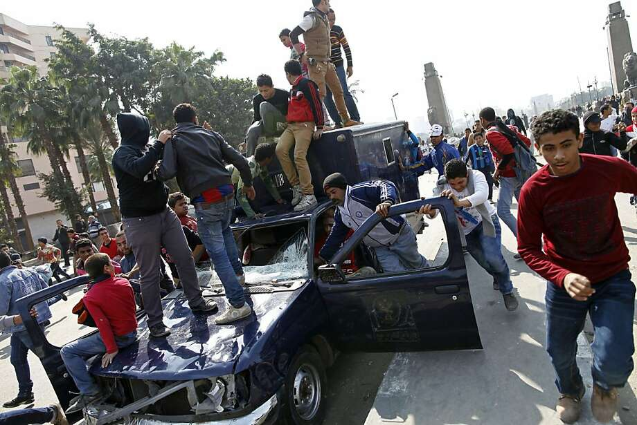 Egyptians vandalize a commandeered police vehicle near Tahrir Square in Cairo, Egypt, Tuesday, March 5, 2013. Skirmishes erupted on Tuesday between street protesters and riot police in a main street overlooking the Nile, a day after protesters set fire to police vehicles in the same area cutting roads and blocking traffic.  Photo: Mahmoud Khaled, Associated Press