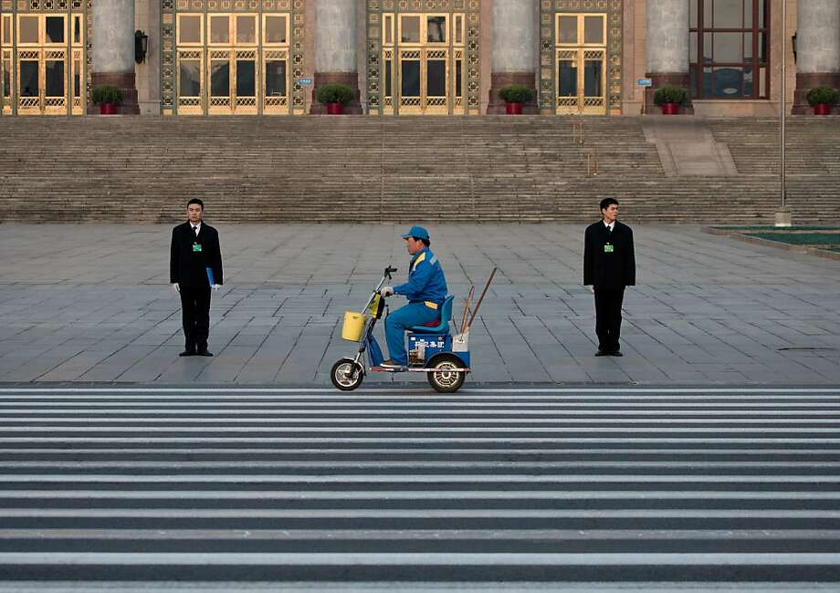 A street cleaner on an electronic bike passes by People's Liberation Army soldiers dressed as ushers while they stand guard in front of the Great Hall of the People before the opening session of the National People's Congress in Beijing Tuesday, March 5, 2013. China's government promised its people Tuesday deficit-fueled spending to fight deep-seated corruption, improve the despoiled environment and address other quality-of-life issues demanded by an increasingly vocal public looking for change. (AP Photo/Andy Wong) Photo: Andy Wong, Associated Press