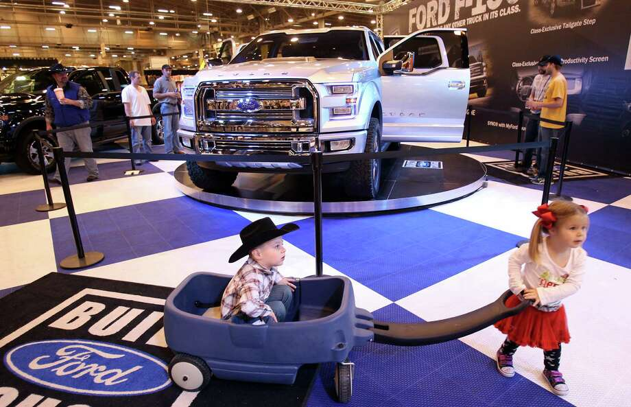 Thomas Garrett is pulled by his sister Clara Garrett as their dad views the Atlas, a concept Ford truck, on display at Reliant Center on Monday, March 4, 2013, in Houston. Photo: Mayra Beltran, Houston Chronicle / © 2013 Houston Chronicle