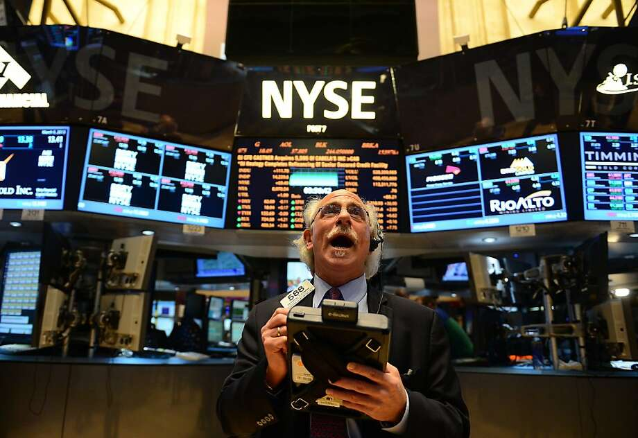 A trader react by the end of trade at the New York Stock Exchange in New York, March 5, 2013. The Dow Jones industrial average surged to a record high at the opening bell, surpassing a key level in its recovery from the 2008 financial meltdown. The Dow Jones closed at 14253.77 points topping the previous record high of 14,164 achieved on October 9, 2007. Photo: Emmanuel Dunand, AFP/Getty Images