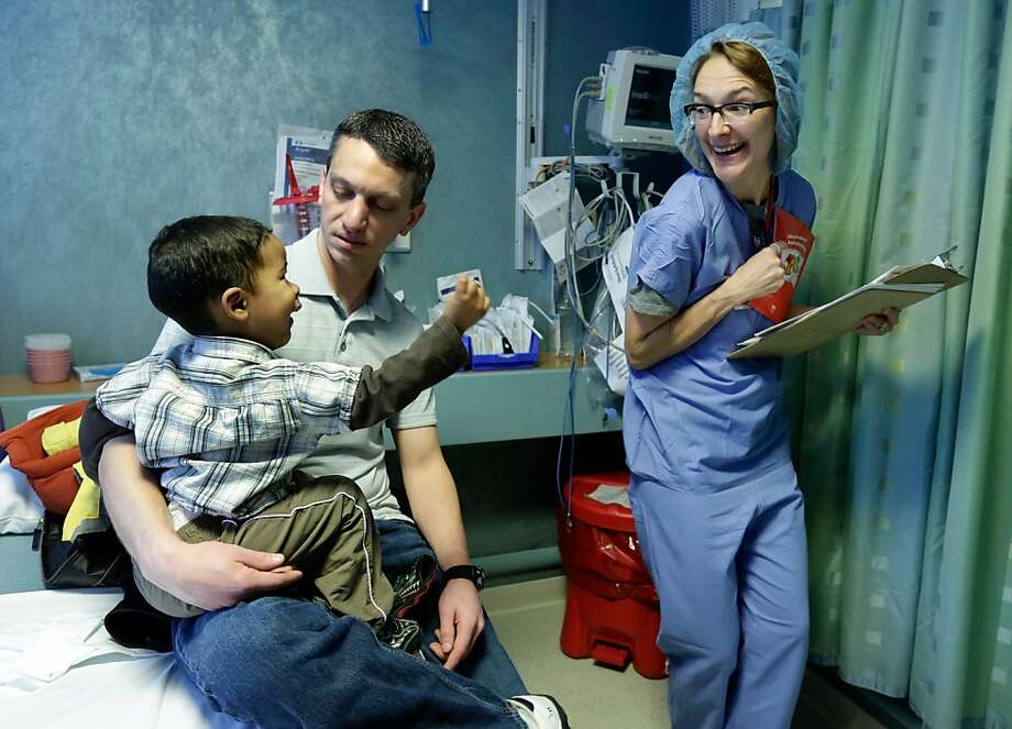 Joel De la Rosa, from the Dominican Republic, sits on the lap of his host Steven Tuorto, of Titusville, N.J., as he meets nurse Patricia Chongtenn, at New York's Roosevelt Hospital, Tuesday, March 5, 2013.  De la Rosa was brought to the United States with the help of the non-profit Healing The Children.  He will be treated for a disfiguring lesion on the left side of his face to cure his lymphatic malformations.  Photo: Richard Drew, Associated Press