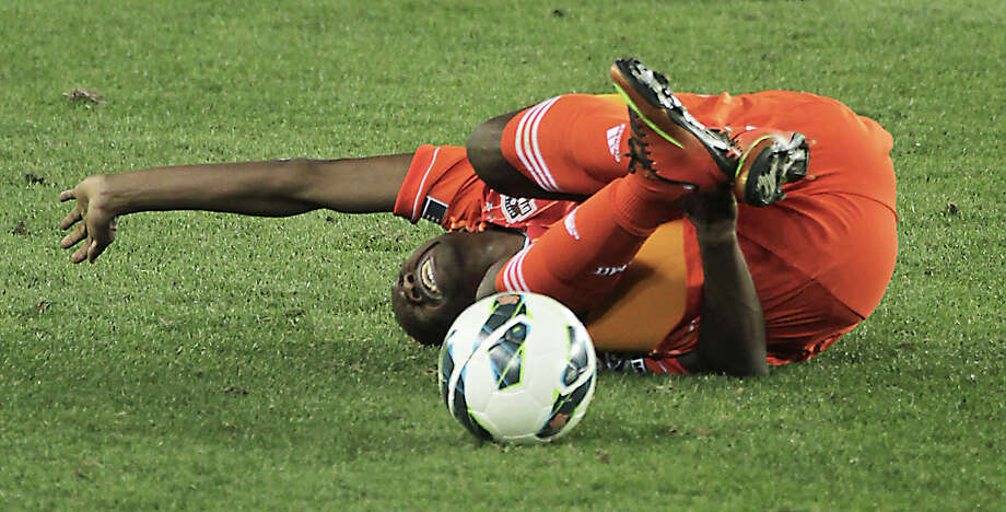 The Houston Dynamo's Boniek Garcia tumbles in pain after a hit from a Santos Laguna player during the second half of the CONCACAF Champions League quarterfinal series game at BBVA Compass Stadium Tuesday, March 5, 2013, in Houston. Photo: James Nielsen, Houston Chronicle / © 2013  Houston Chronicle