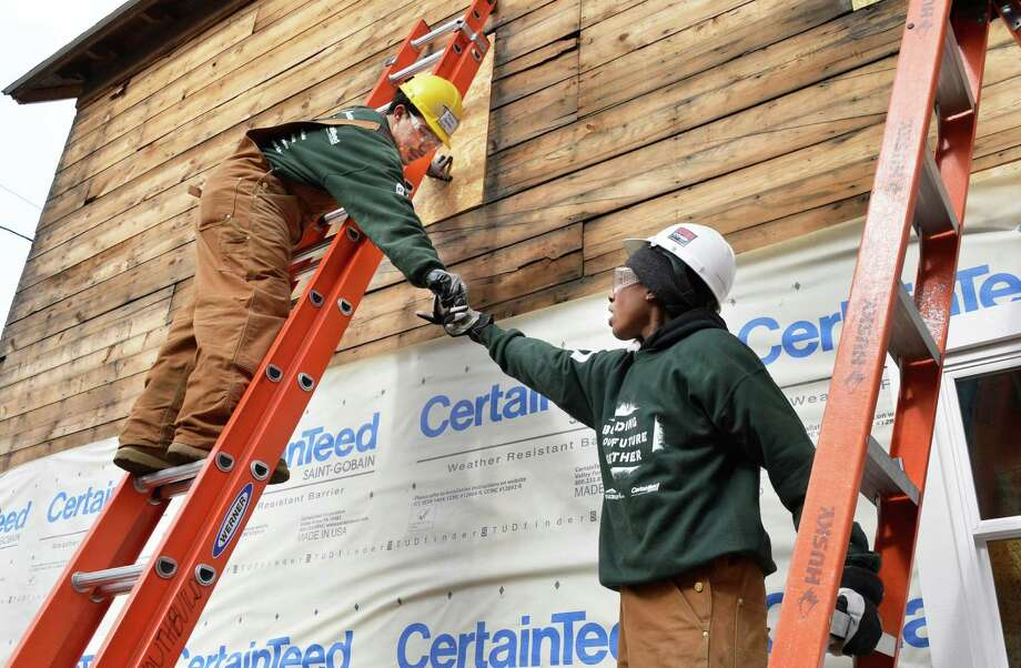 Students from Northeast Parent & Child Society?s YouthBuild Schenectady, Tomas Sanchez, 23, left, and Tendaya Gamble, 24,  put up siding under the supervision of a team from Saint-Gobain Abrasives in Watervliet, on the sustainable rehab project in the Hamilton Hill neighborhood of Schenectady Tuesday May 5, 2013.  (John Carl D'Annibale / Times Union) Photo: John Carl D'Annibale / 10021405A
