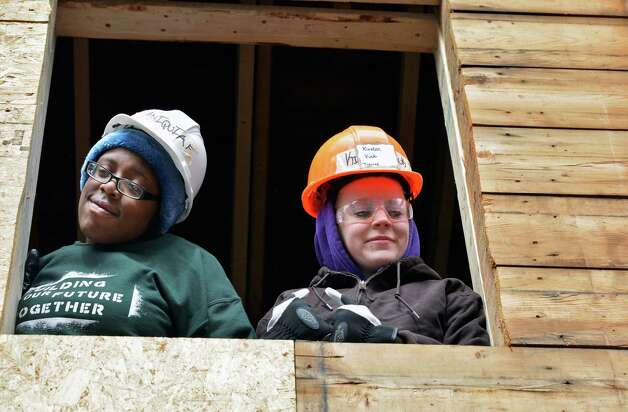 Students from Northeast Parent & Child Society?s YouthBuild Schenectady Aniqa Fielder, l20, left, and Kirsten Vink, 18, look down from an upstairs window as students and a team from Saint-Gobain Abrasives in Watervliet, work on the sustainable rehab project in the Hamilton Hill neighborhood of Schenectady Tuesday May 5, 2013.  (John Carl D'Annibale / Times Union) Photo: John Carl D'Annibale / 10021405A