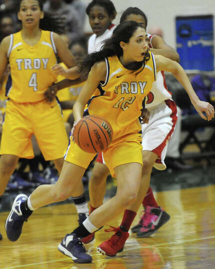 Courtney Avery of Troy dribbles around  J-D defenders in second half action at Le Moyne College.  (M