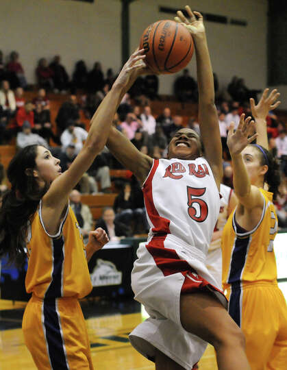 Cydney Goodrum of J-D at center loses possession between Troy defenders Courtney Avery at left and K