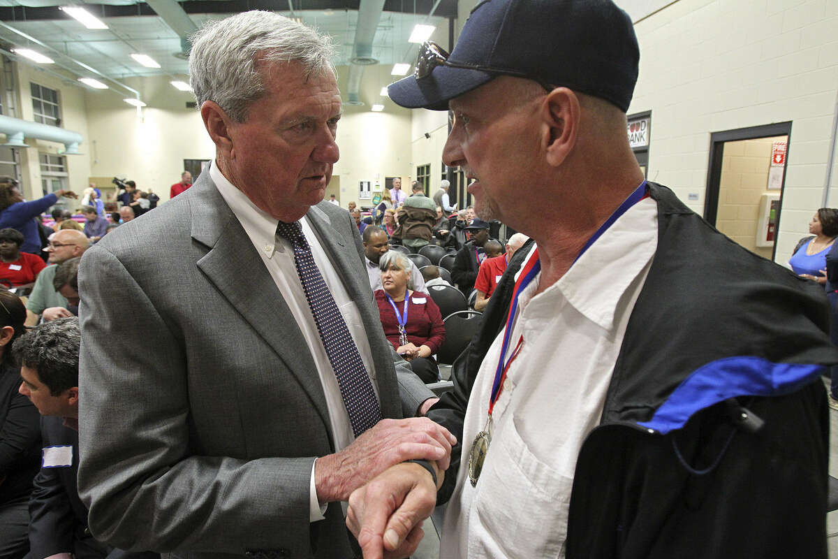 Haven for Hope founder Bill Greehey (left) talks with graduate Ralph Wooster during a ceremony to mark the campus getting 1,000 people into permanent housing.