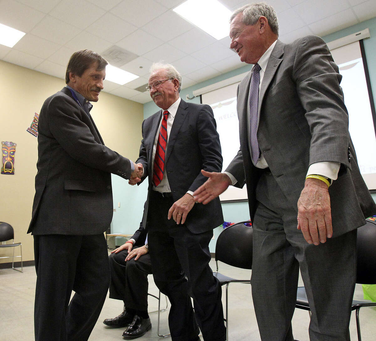 Evan Benton, one of Haven's first graduates, who spoke at the event, shakes hands with former Mayor Phil Hardberger and Haven founder Bill Greehey.