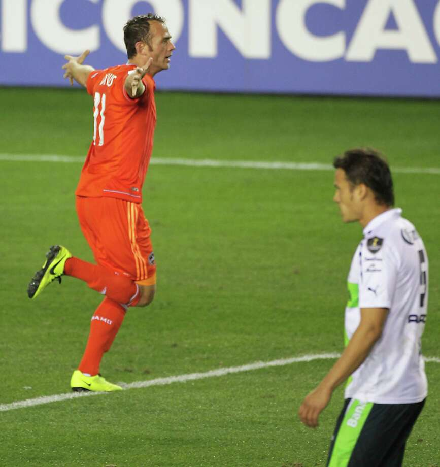 The Houston Dynamo's Brad Davis left, celebrates after scoring a goal as Santos Laguna's Aaron Galindo right, walks away during the second half of the CONCACAF Champions League quarterfinal series game at BBVA Compass Stadium Tuesday, March 5, 2013, in Houston. Photo: James Nielsen, Houston Chronicle / © 2013  Houston Chronicle