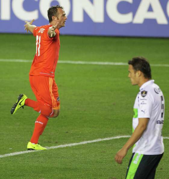 The Houston Dynamo's Brad Davis left, celebrates after scoring a goal as Santos Laguna's Aaron Galin