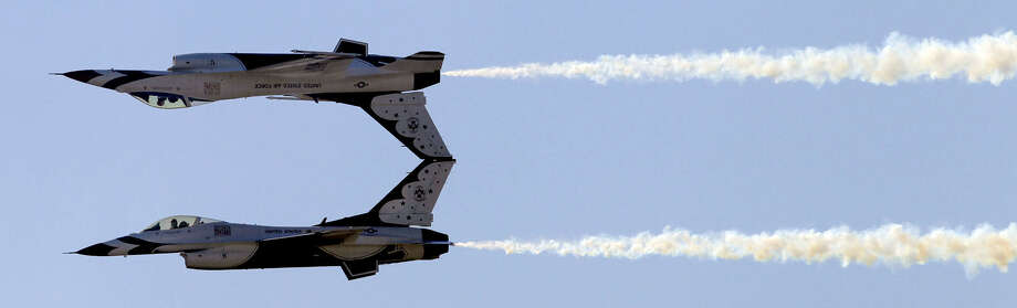 Two Air Force Thunderbirds jets fly in a mirror-image pattern during the local air show in 2010. Photo: San Antonio Express-News File Photo