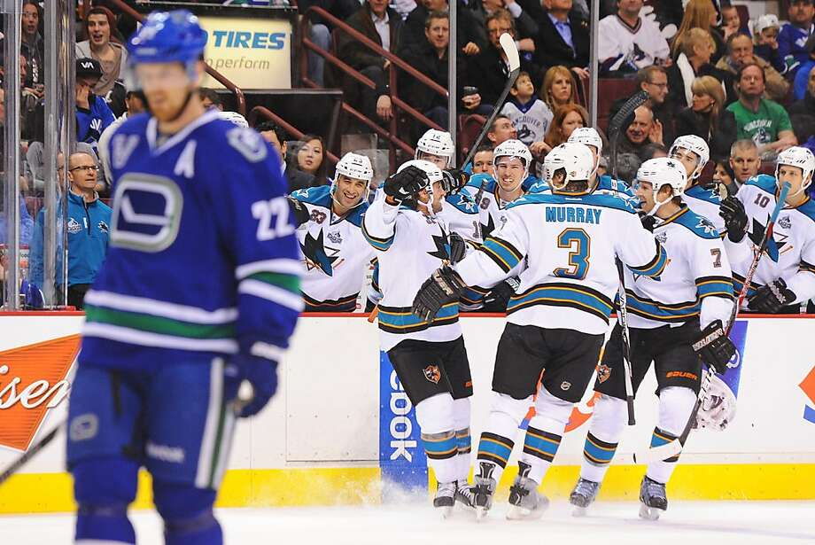 San Jose's Adam Burish (center) raises his stick in the air to celebrate his first goal in 45 games. Photo: Derek Leung, Getty Images