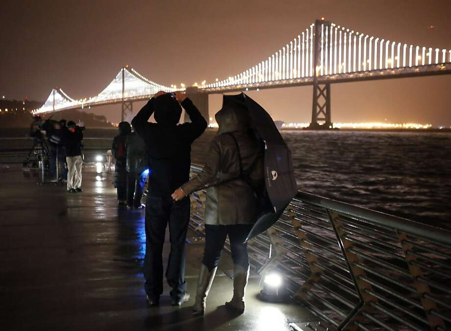 Doug Valchar, left, and his girlfriend Eleni Courcoumelis watch as the Bay Lights illuminated the cables on the Bay Bridge on Tuesday night. San Franciscans watched the lighting of the Bay Lights art project on Tuesday, March 5, 2013, which illuminated the bridge with thousands of LED lights from the structural cables. Photo: Carlos Avila Gonzalez, The Chronicle