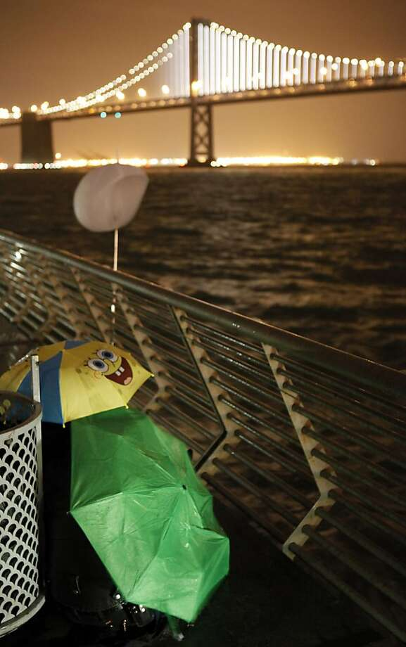 James Thomassen of San Jose, and Holly Lovato of Sunnyvale, took shelter under umbrellas to watch as the Bay Lights illuminated the cables on the Bay Bridge on Tuesday night. San Franciscans watched the lighting of the Bay Lights art project on Tuesday, March 5, 2013, which illuminated the bridge with thousands of LED lights from the structural cables. Photo: Carlos Avila Gonzalez, The Chronicle