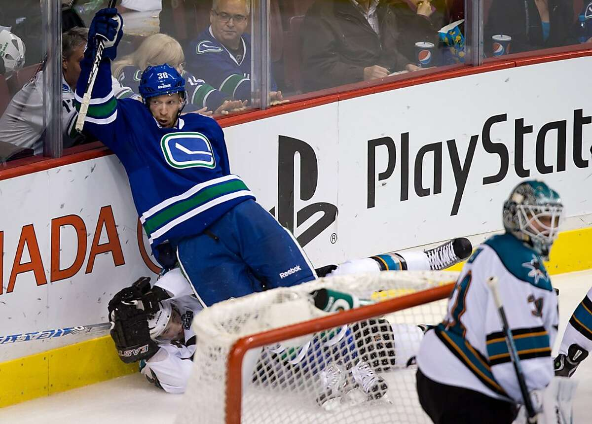 Vancouver Canucks' Jannik Hansen, of Denmark, checks San Jose Sharks' Marc-Edouard Vlasic, left, during the third period of an NHL hockey game in Vancouver, British Columbia, Tuesday, March 5, 2013. (AP Photo/The Canadian Press, Darryl Dyck)