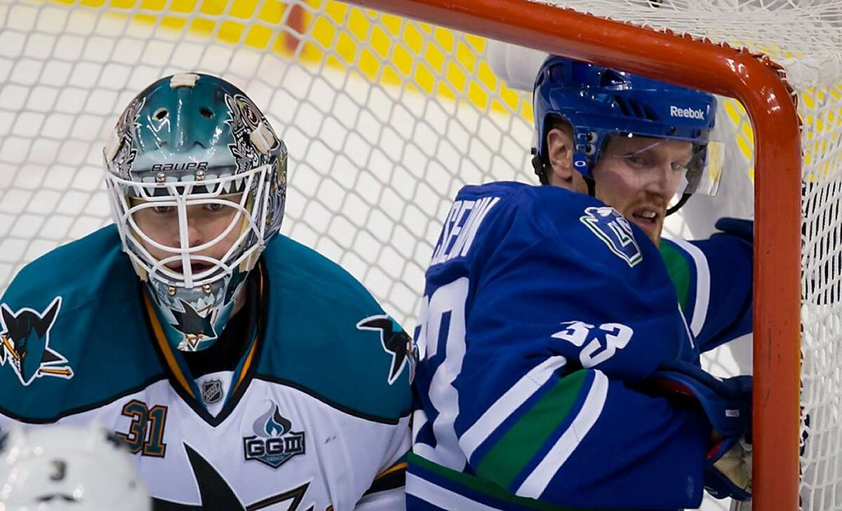 Vancouver Canucks' Henrik Sedin, right, of Sweden, gets up after crashing into the net behind San Jose Sharks' goalie Antti Niemi, of Finland, during the second period of an NHL hockey game in Vancouver, British Columbia, Tuesday, March 5, 2013. (AP Photo/The Canadian Press, Darryl Dyck)