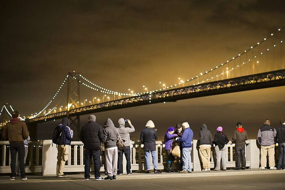SAN FRANCISCO, CA - MARCH 5: A group of people watch the grand lighting of the Bay Lights art installation on the San Francisco-Oakland Bay Bridge on March 5, 2013 in San Francisco, California. Designed by artist Leo Villareal, the Bay Lights is the world's largest LED light sculpture, spanning 1.8 miles long and 500 feet high with 25,000 individual LED lights. The installation will be on display daily from dusk to 2 a.m. for the next two years (Photo by Stephen Lam/Getty Images) Photo: Stephen Lam, Getty Images