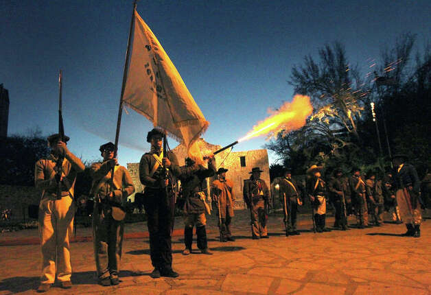 "A member of the San Antonio Living History Association fires a musket (center) as others stand at attention Wednesday March 6, 2013 in front of the Alamo during the ""Dawn at the Alamo"" ceremony on the 177th anniversary of the battle for Texas independence. About 300 to 500 Mexican troops are said to have been killed or wounded in the battle and at least 189 Alamo defenders died in the battle or were executed. Photo: JOHN DAVENPORT, San Antonio Express-News / ©San Antonio Express-News/Photo Can Be Sold to the Public"