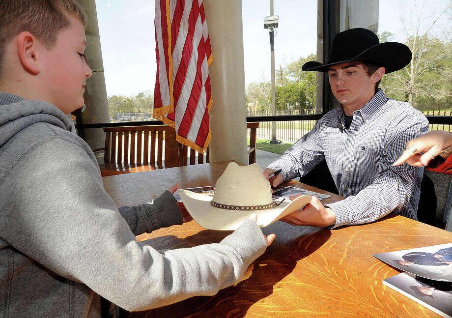 Nate Roth hands over a cowboy hat to Cody Teel for a signature at the Kountze County Courthouse on Tuesday. Originally from Kountze, Teel toured the town Tuesday after becoming a world championship bull rider earlier this year. Photo taken Tuesday, March 5, 2013 Guiseppe Barranco/The Enterprise Photo: Guiseppe Barranco, STAFF PHOTOGRAPHER / The Beaumont Enterprise