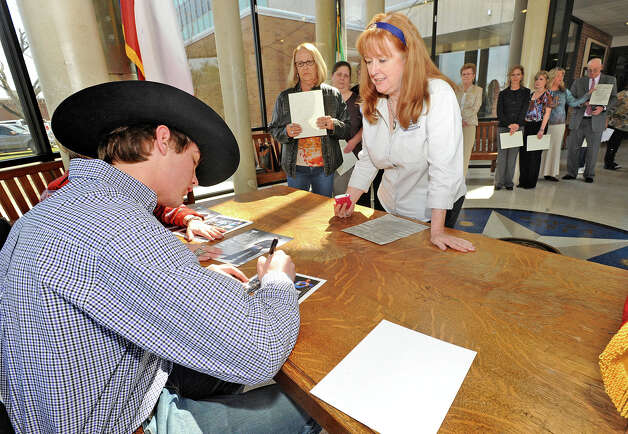 Cody Teel autographs a form for Esther Scarborough at the Hardin County Courthouse on Tuesday. The word champion bull rider returned to Kountze to be recognized by the town. Photo taken Tuesday, March 5, 2013 Guiseppe Barranco/The Enterprise Photo: Guiseppe Barranco, STAFF PHOTOGRAPHER / The Beaumont Enterprise