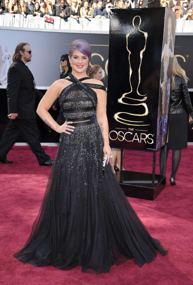 Kelly Osbourne wears a black gown with silver embellishments. The criss-cross top is great for those with broad shoulders. I'd suggerst staying away from the peach lipstick though. (Photo by John Shearer/Invision/AP)