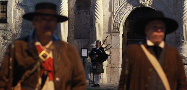 "A bagpiper (center, background) plays Wednesday March 6, 2013 in front of the Alamo during the ""Dawn at the Alamo"" ceremony on the 177th anniversary of the battle for Texas independence. About 300 to 500 Mexican troops are said to have been killed or wounded in the battle and at least 189 Alamo defenders died in the battle or were executed. Photo: JOHN DAVENPORT, San Antonio Express-News / ©San Antonio Express-News/Photo Can Be Sold to the Public"
