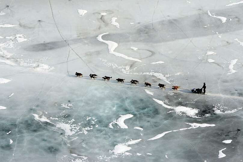 A musher and dog team cross the ice between the Rohn and Nikolai checkpoints in Alaska during the Id