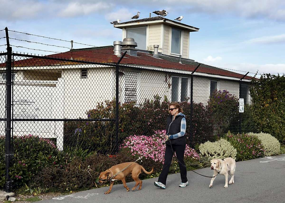 A woman walks her dog in front of the old, abandoned U.S. Naval Magnetic Silencing Range Building on the Marina Green. Nearby residents in San Francisco, Calif., are none too happy with a proposed restaurant at the building. Some are even taking to putting signs up in there homes showing their opposition.