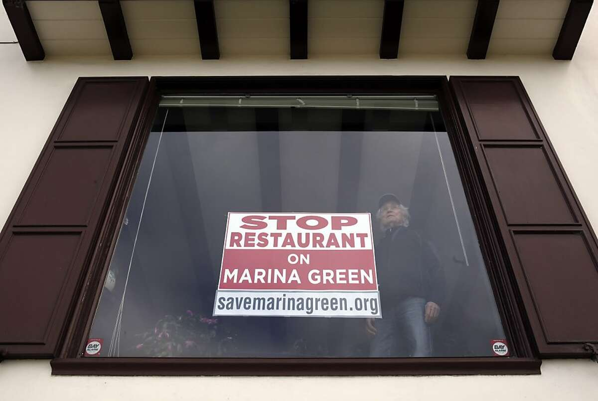 Art Scampa looks out the window of his Marina Blvd., home on Tuesday, March 5, 2013, in San Francisco, Calif. Residents near the Marina Green in San Francisco, Calif., are none too happy with a proposed restaurant at the old, abandoned U.S. Naval Magnetic Silencing Range Building. Some are even taking to putting signs up in there homes showing their opposition.