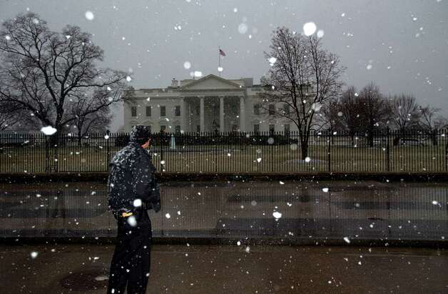 A member of the Secret Service keeps watch outside the White House as snow begins to fall in Washington, March 6, 2013. The federal government closed offices in Washington Wednesday as heavy, slushy snow was forecasted for the area. (Doug Mills/The New York Times) Photo: DOUG MILLS / NYTNS