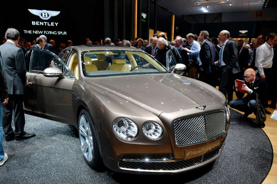 People discover the new Bentley Flying Spur at the Geneva International Motor Show on March 5, 2013 which opens its doors today under a dark cloud, with no sign of a speedy rebound in sight for the troubled European market. The event, which is considered one of the most important car shows of the year, will again be heavily marked by the crisis in Europe after an already catastrophic year in 2012. AFP PHOTO / SEBASTIEN FEVALSEBASTIEN FEVAL/AFP/Getty Images Photo: SEBASTIEN FEVAL, AFP/Getty Images / AFP