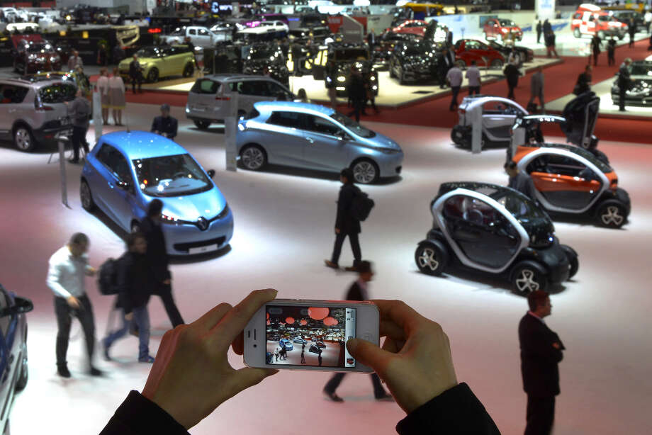 A person takes a picture of cars on March 5, 2013 on the press day of the Geneva car Show in Geneva. The Geneva International Motor Show opens its doors under a dark cloud, with no sign of a speedy rebound in sight for the troubled European market. The event, which is considered one of the most important car shows of the year, will again be heavily marked by the crisis in Europe after an already catastrophic year in 2012.  AFP PHOTO / SEBASTIEN FEVALSEBASTIEN FEVAL/AFP/Getty Images Photo: SEBASTIEN FEVAL, AFP/Getty Images / AFP