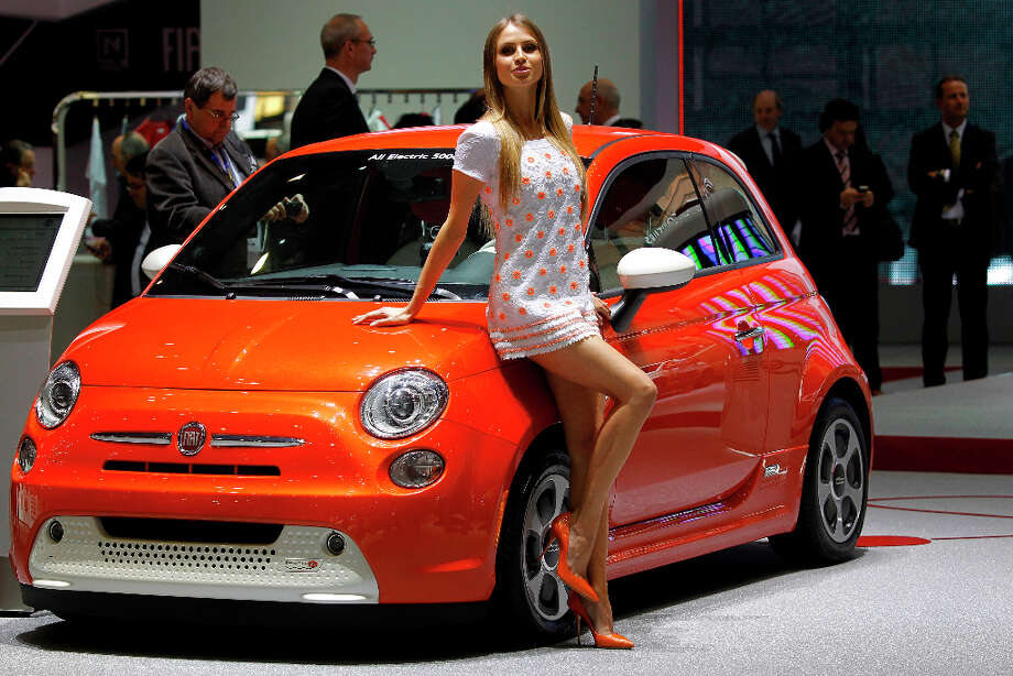 A hostess poses in front of a Fiat 500 during the first media day of the 83rd Geneva International Motor Show, Switzerland, Tuesday, March 5, 2013. The Motor Show will open its gates to the public from March 7 to 17.  (AP Photo/Laurent Cipriani) Photo: Laurent Cipriani, Associated Press / AP
