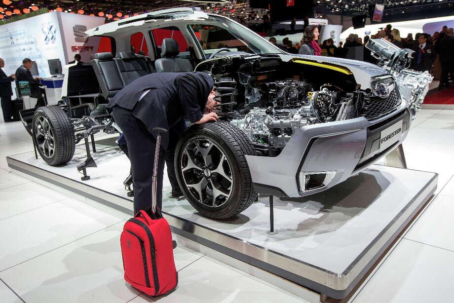 A journalist looks at a wheel of a Forester at the Subaru booth, during the press day at the 83rd Geneva International Motor Show in Geneva, Switzerland, Tuesday, March 5, 2013. The Motor Show will open its gates to the public from 7th to 17th March presenting more than 260 exhibitors and more than 130 world and European premieres. (AP Photo/Keystone, Salvatore Di Nolfi) Photo: Salvatore Di Nolfi, Associated Press / Keystone