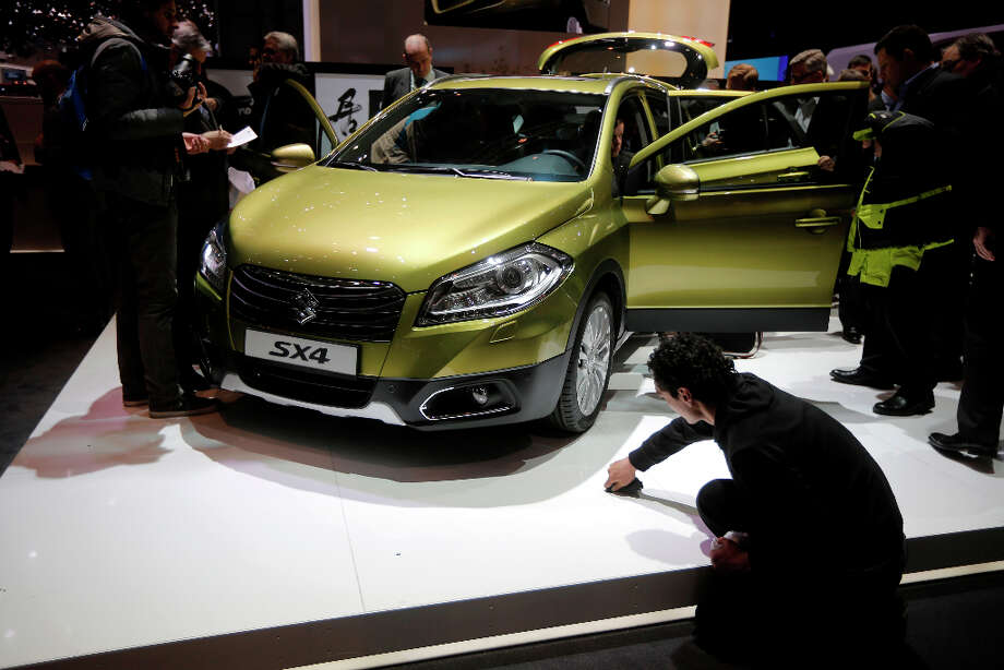 People look at the Suzuki SX4 during the first media day of the 83rd Geneva International Motor Show, Switzerland, Tuesday, March 5, 2013. The Motor Show will open its gates to the public from March 7 to 17.  (AP Photo/Laurent Cipriani) Photo: Laurent Cipriani, Associated Press / AP