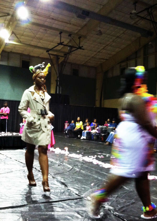 Models Britney Porter, 25, and Kalisha Buchanan, 26, strut their stuff in a style show Saturday at the Curling for the Community Hair Show at the L.L. Melton Community Center. Photo: Sarah Moore