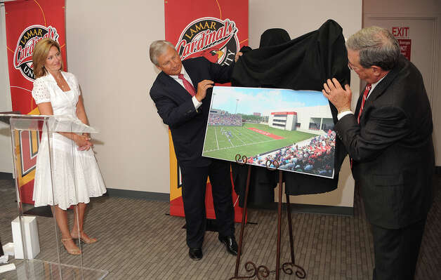 Glen Morgan assists Jimmy Simmons in unveiling a rendering of a the upcoming Morgan Suits at Lamar's football field. Attached to the South end of the Montagne Center, the suites will look over the field costing consumers $25,000 a year in a three year contract. Guiseppe Barranco/The Enterprise