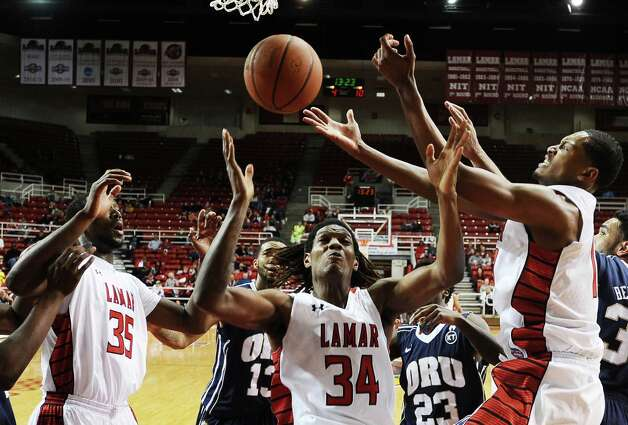 Lamar players Stan Brown, Amos Wilson, and Rhon Mitchell fight for a rebound during the Lamar University mens basketball game against Oral Roberts University at the Montagne Center on March 2, 2013.  Oral Roberts won over Lamar 68 - 50. Photo taken: Randy Edwards/The Enterprise