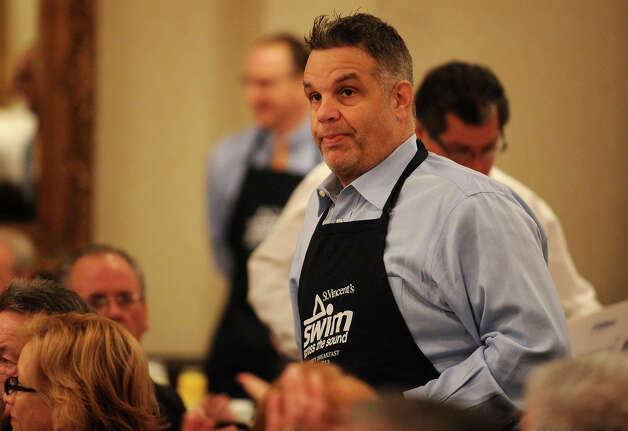 Vazzy's restauranteur John Vazzano listens as UCONN women's basketball Coach Geno Auriemma addresses the annual Swim Across the Sound fundraising breakfast at the Holiday Inn in Bridgeport, Conn., on Wednesday, March 6, 2013. Photo: Brian A. Pounds / Connecticut Post