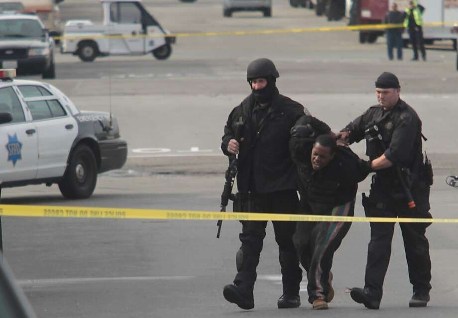 Police arrest a man suspected of taking part in the attempted robbery and hostage-taking at a marijuana- growing operation in San Francisco. Four hostages were unharmed; four suspects were arrested. Photo: Mathew Sumner, Special To The Chronicle