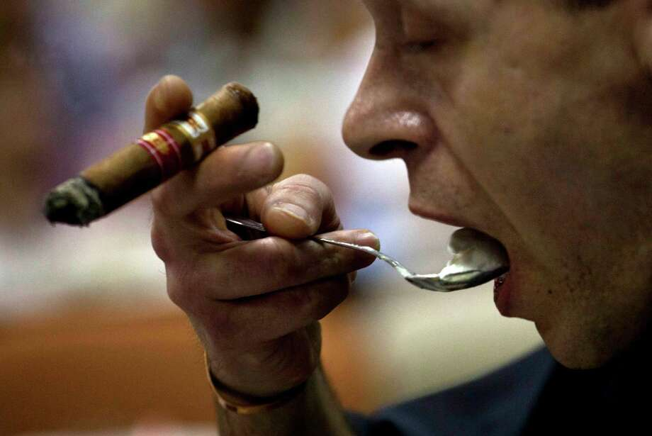 A man eats a dessert as he smokes a cigar during a cooking event at the 15th Cigar Festival in Havana, Cuba, Thursday, Feb. 28, 2013. A team of Croatian chefs whipped up a pungent meal Thursday, infusing the flavor of the tobacco leaf synonymous with Cuba into baked stone bass filets, bread and butter, a rich demi-glace sauce, even ice cream. (AP Photo/Ramon Espinosa) Photo: Ramon Espinosa / AP