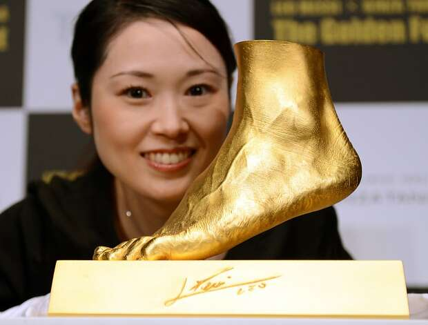 Japanese welcome athlete's foot: Tokyo jewelry retailer Ginza Tanaka created this life-sized golden replica of soccer star Lionel Messi's left foot. The shiny appendage, worth about $5.2 million, weighs 55 pounds. Photo: Toshifumi Kitamura, AFP/Getty Images