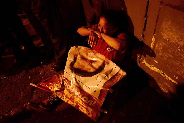 Mourning el presidente: A supporter of Hugo Chavez weeps outside the Military Hospital in Caracas after learning of the  Venezuelan president's death. Chavez, who lost a long battle with cancer, was the leading voice of the Latin American left. Photo: Leo Ramirez, AFP/Getty Images