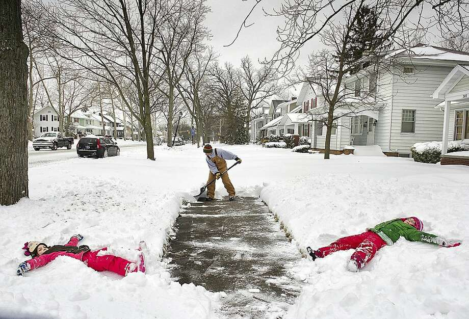 Exhausted angels: Jason Smith clears a path between a couple of snow angel makers - daughters Kylie and Alexa - while shoveling the sidewalk in front of his home in Fort Wayne, Ind. Photo: Swikar Patel, Associated Press
