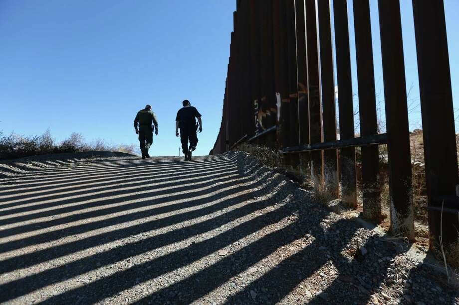 U.S. Customs and Border Protection personnel walk along a section of the recently constructed fence Feb. 26 at the U.S.-Mexico border in Nogales, Arizona. Photo: Getty Images