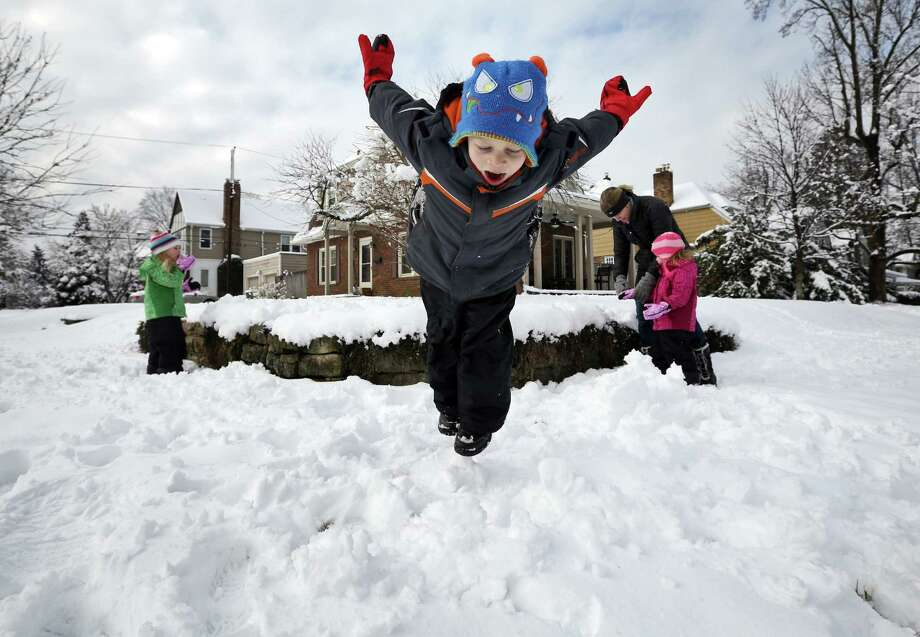 Johnny Connell, 5, takes a dive into the snow while his twin sisters Christine and Sammy, 3, and mother Megan Connell play in the yard across from their home in Clintonville, Ohio on Wednesday, March 6, 2013.  A  late-winter storm dumped a half-foot or more of snow across much of Ohio. Photo: Adam Cairns, Associated Press / The Columbus Dispatch