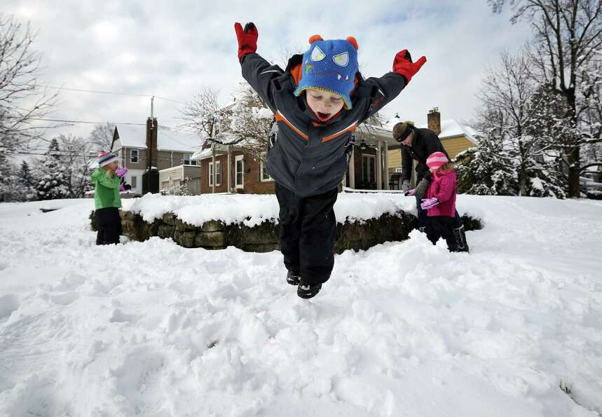 Johnny Connell, 5, takes a dive into the snow while his twin sisters Christine and Sammy, 3, and mot
