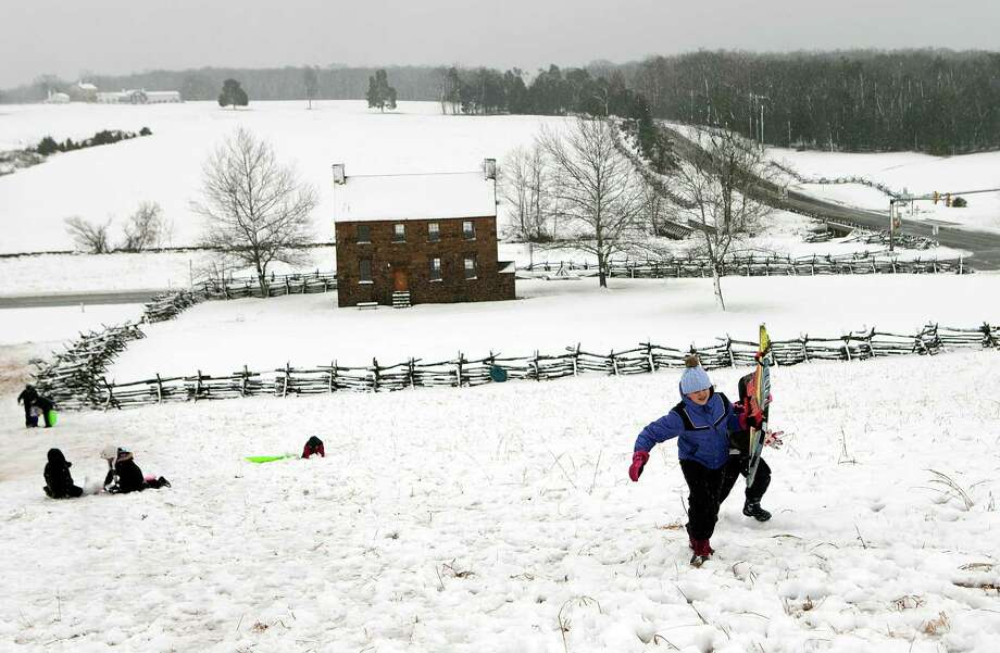 Annie Castro (L) and Sophia Benedetto battle gusting winds and snow to reach the top of a sledding hill on the grounds of Manassas Battlefield Park March 6, 2013 in Manassas, Virginia. A winter storm hit the Washington, DC area today with areas west of the city seeing signficant snowfall, but the city itself seeing minimal snow. Photo: Win McNamee, Getty Images / 2013 Getty Images