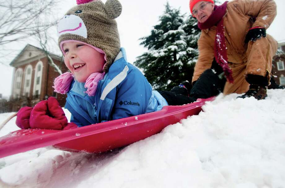 Frankie Bryant holds his granddaughter Reagan Bryant's sled at a hill on the campus of Sweet Briar College on Wednesday March 6, 2013 at in Amherst, Va.  Snow covered much of the area leaving thousands without power. Photo: Jill Nance, Associated Press / THE NEWS & ADVANCE